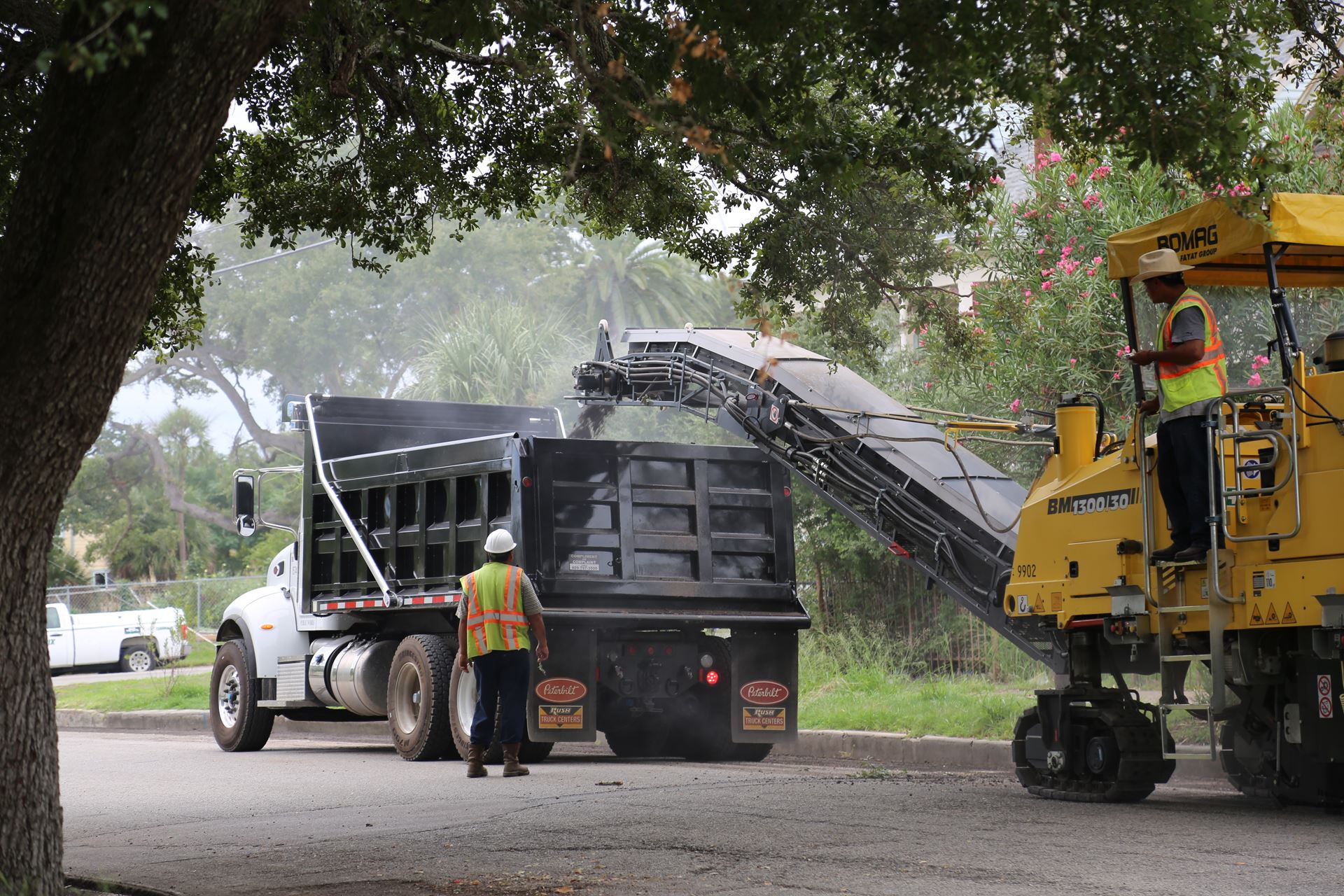 Pavement Milling Machine Dumping Asphalt into Dump Truck